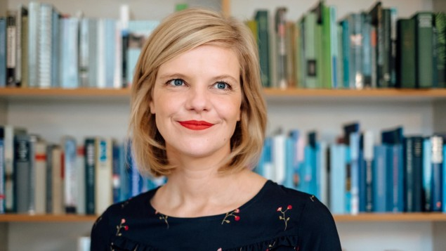 Seorang wanita berambut pirang dengan lipstik berdiri di depan rak buku.  (Nicole Shore)