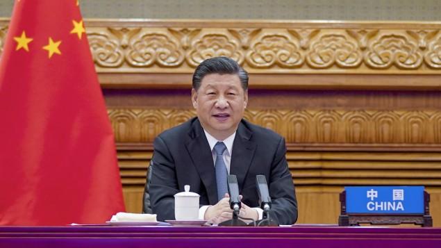 Presiden China Xi Jinping duduk di meja dengan mikrofon selama konferensi video pada bulan April.  (Aliansi / Kantor Berita Xinhua / foto Li Xueren)