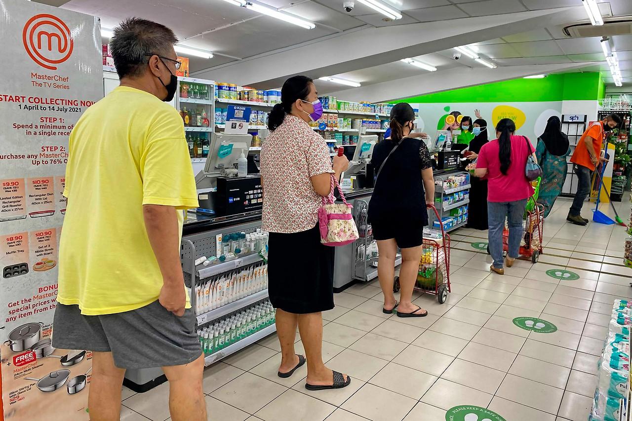 Orang-orang mengantri di supermarket di Singapura