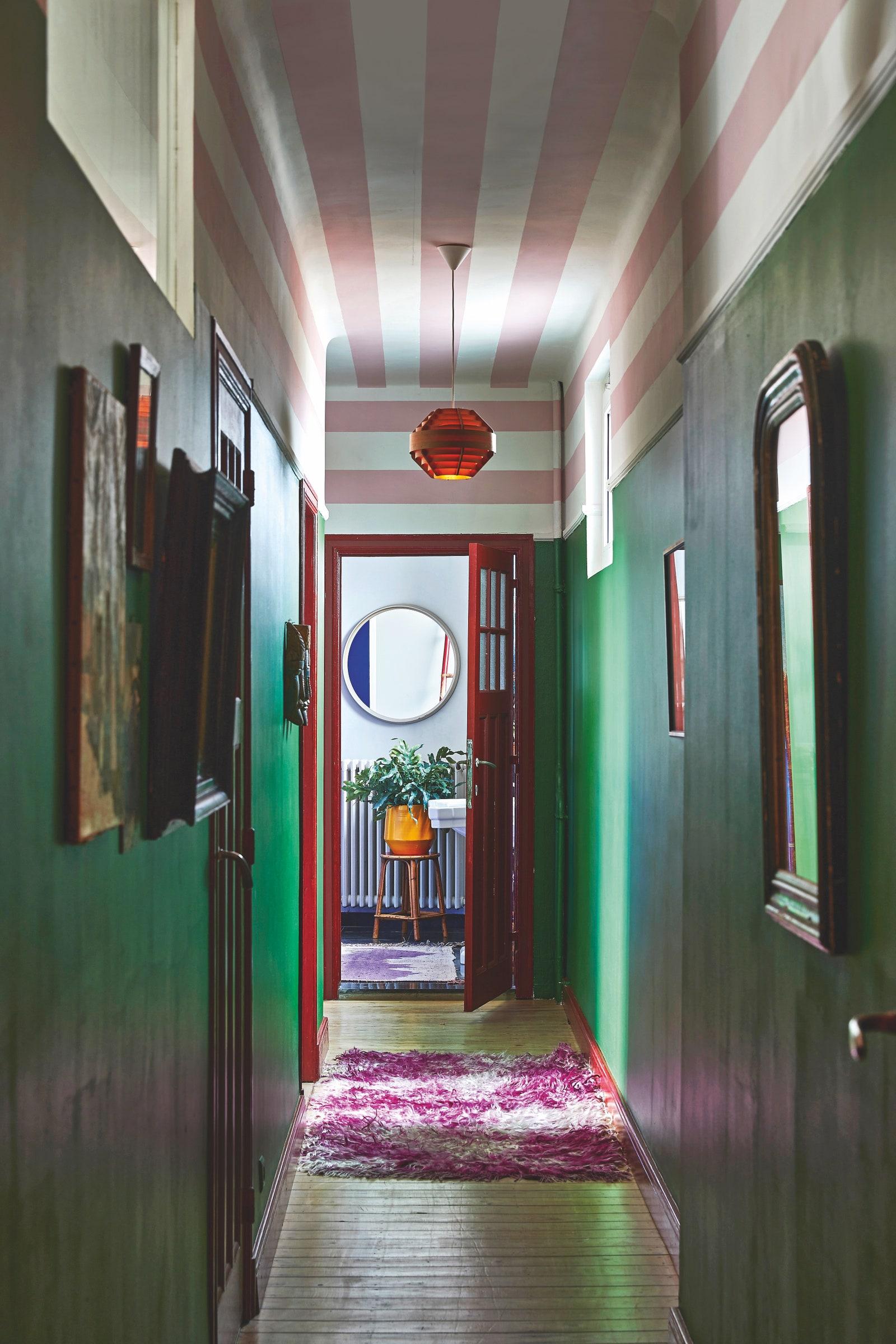 Lihatlah ke lorong di sepanjang dinding hijau dan garis-garis merah muda yang dipenuhi gambar dan cermin.