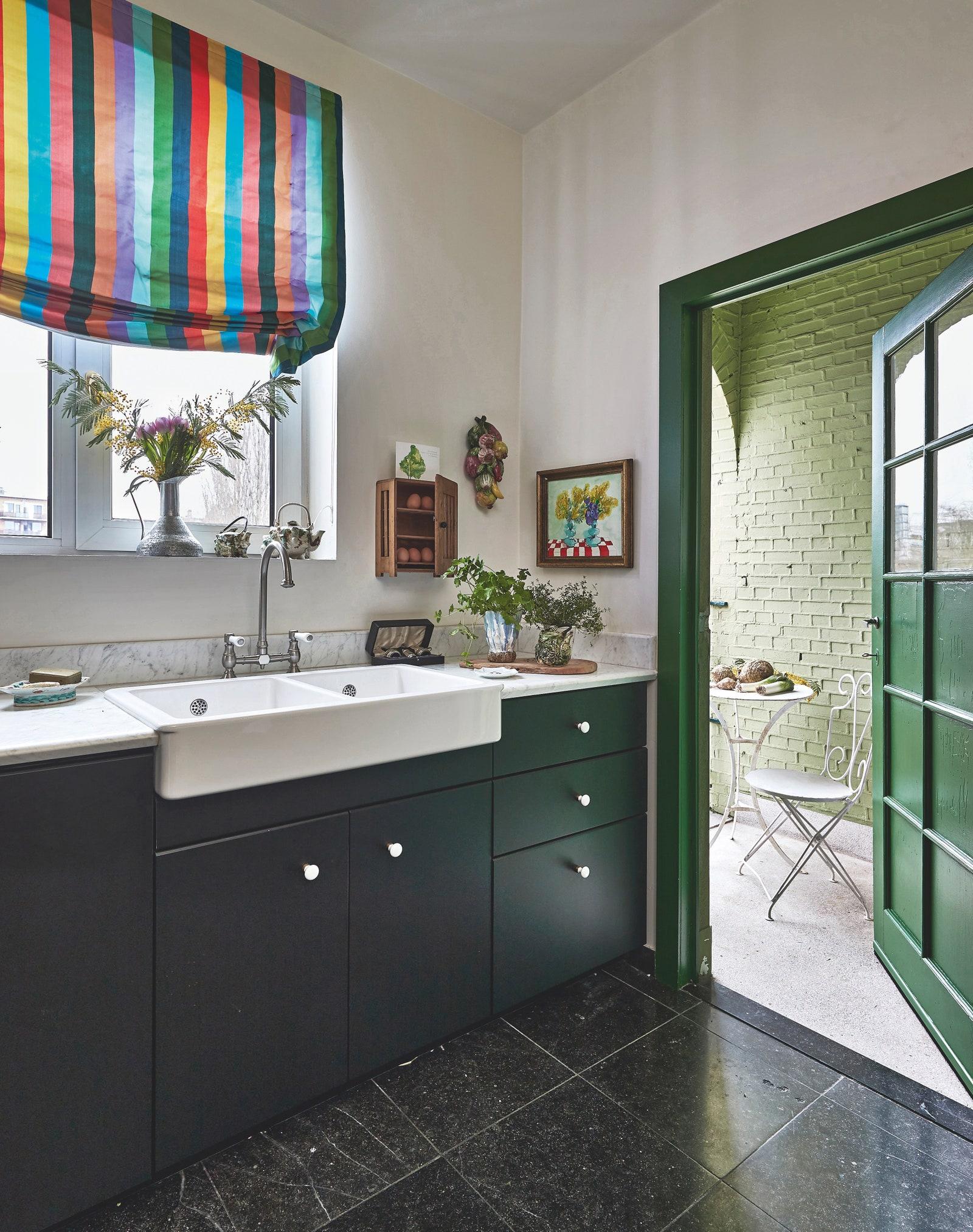 Dapur hijau rumah dengan tirai berwarna dan pintu hijau terbuka menunjukkan balkon yang bersebelahan.