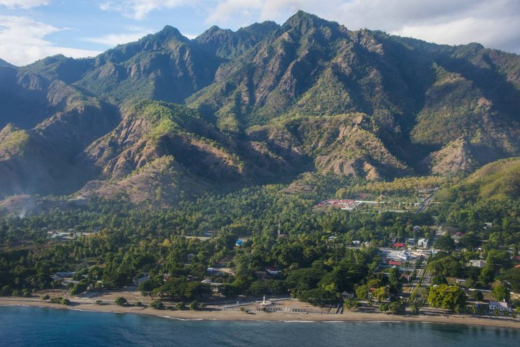 Pemandangan pantai Timor Timur dengan latar belakang pantai dan pegunungan.